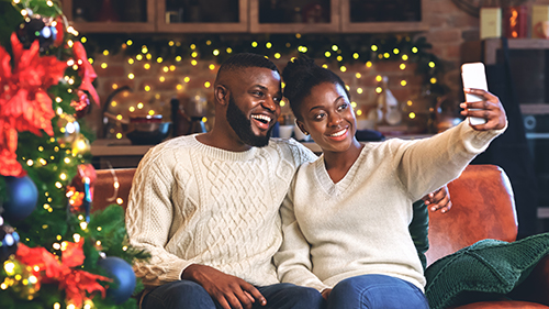 Happy couple celebrating Christmas fairy light social distancing festive red green Christmas tree knitted sweaters