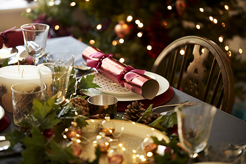 Christmas table setting decór with Christmas tree and fairy lights and Christmas cracker classy elegant